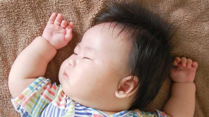 布団で寝てるお肉がむちむちな赤ちゃん