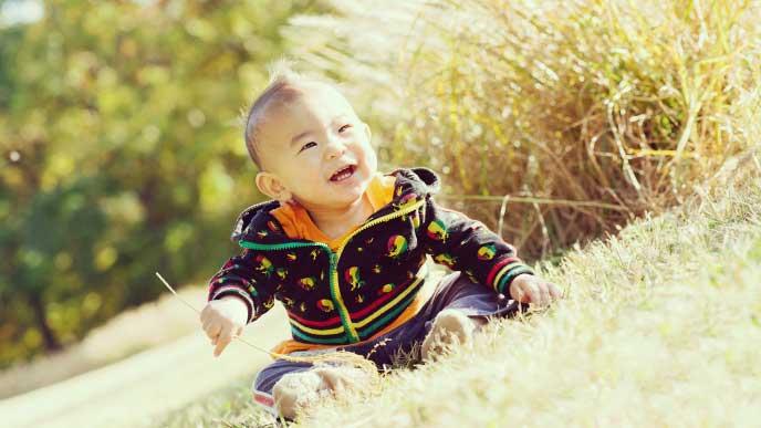 原っぱで座ってる笑顔の赤ちゃん