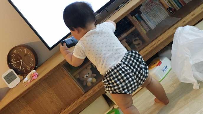つかまり立ちをしてるオムツをしてる赤ちゃん
