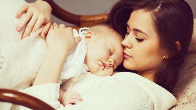 生後1ヶ月の赤ちゃんを抱っこして寝てるママ