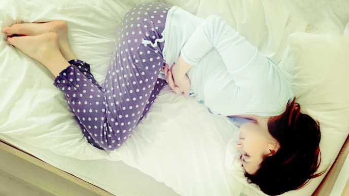 下腹部を押さえてベッドで横になっている女性