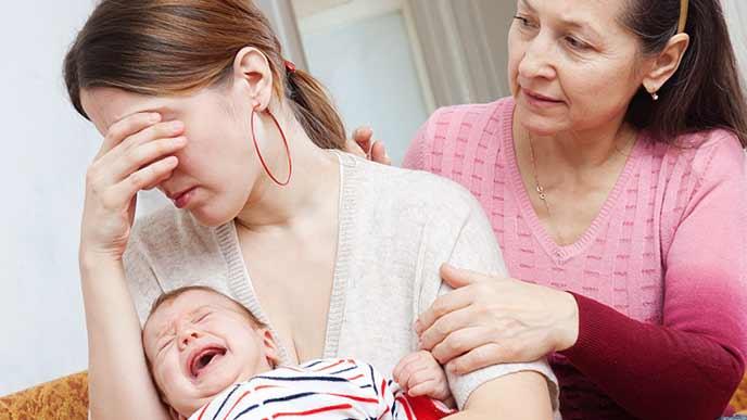 赤ちゃんを抱きながら落ち込む女性
