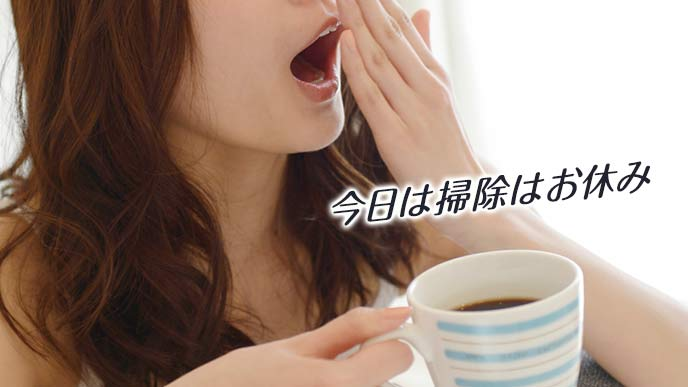 コーヒーを飲みながら欠伸する女性