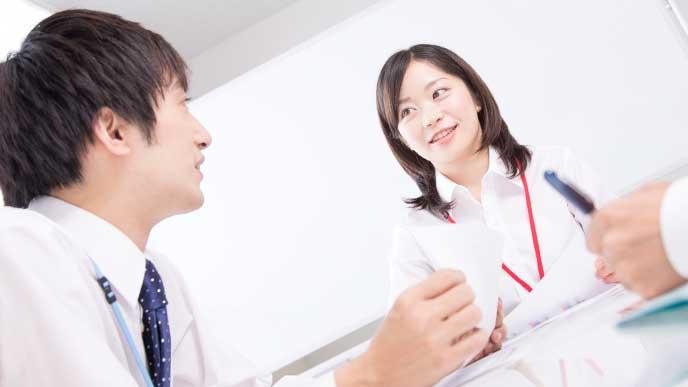 同僚に妊娠の報告をする女性社員