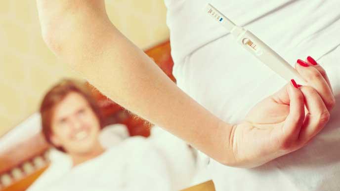 陽性の妊娠検査薬を後手に隠して旦那さんを驚かせようとしてる奥さん