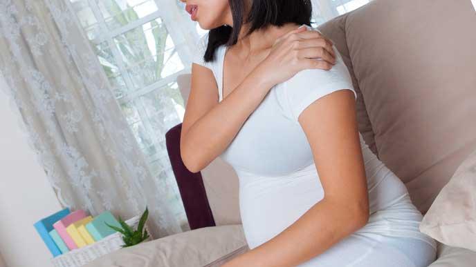疲れて肩をおさえている妊婦さん