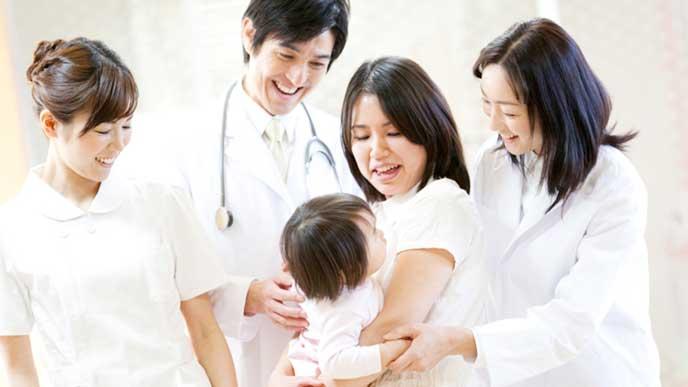 赤ちゃんを抱っこしてる母親を笑顔で見てる産婦人科のスタッフたち