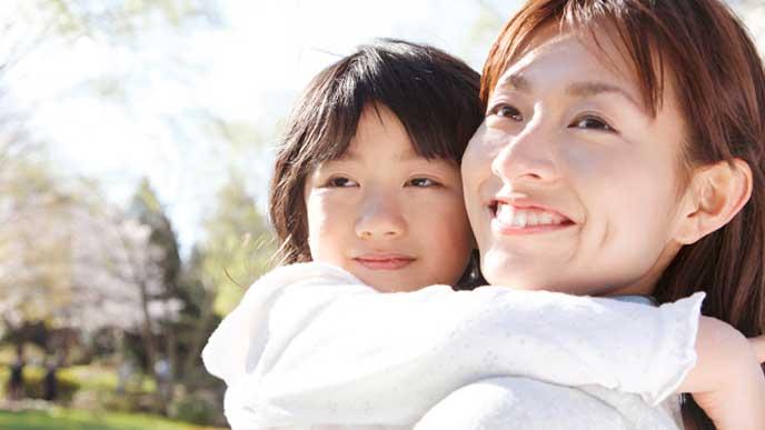 3歳児の娘を抱っこする母親
