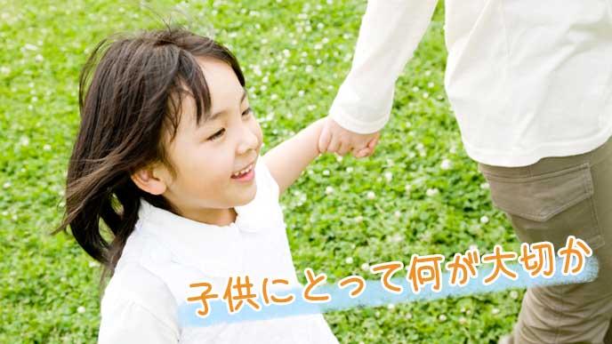 野原で母親と一緒に手を繋ぐ3歳児の女の子