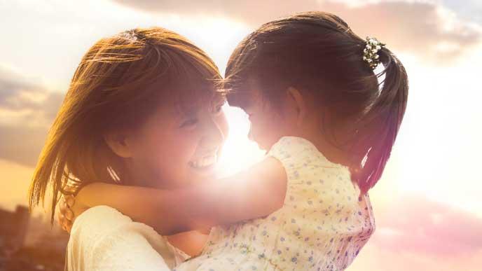 夕日の下で笑顔で自分の子供を抱っこする母親