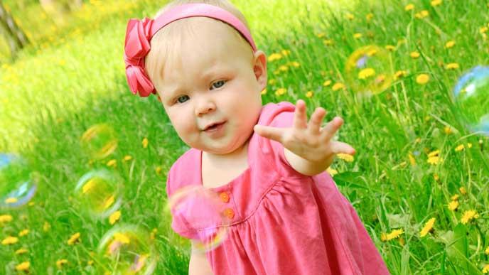 草原の上でシャボン玉をつかもうとして遊ぶ赤いセレモニードレスを着た赤ちゃん