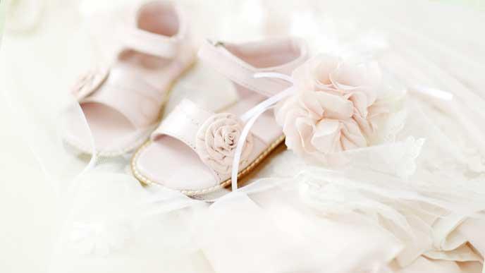 白いセレモニードレスと薄いピンク色の赤ちゃん用の靴と花の形をした髪飾り