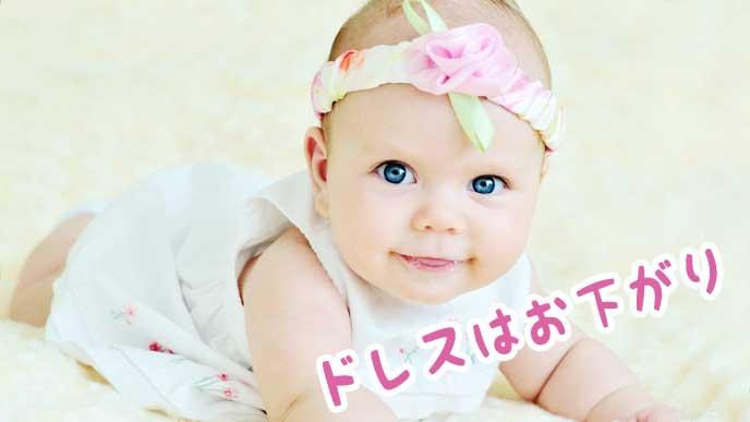 お下がりのベビードレスを着たハイハイしている赤ちゃん