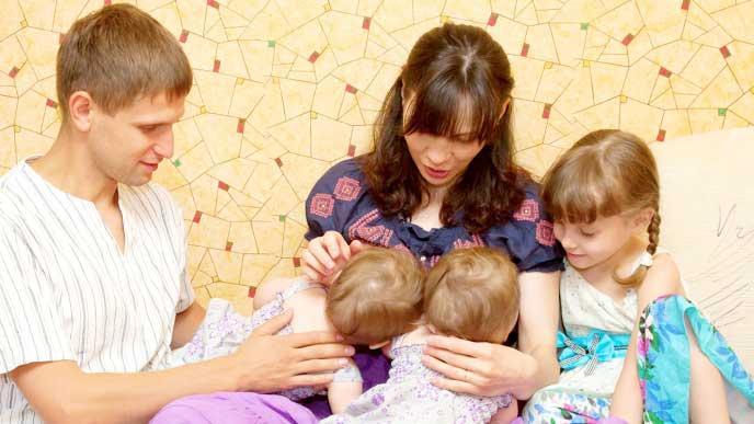 双子の赤ちゃんにタンデム授乳をする母親と横から見守る夫と娘