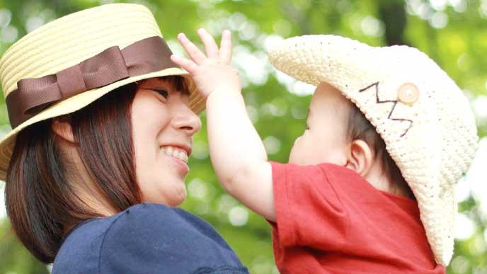 一緒に麦わら帽子を被る母親と赤ちゃん