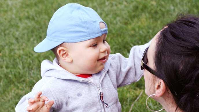 水色の帽子をかぶる赤ちゃんと褒める母親