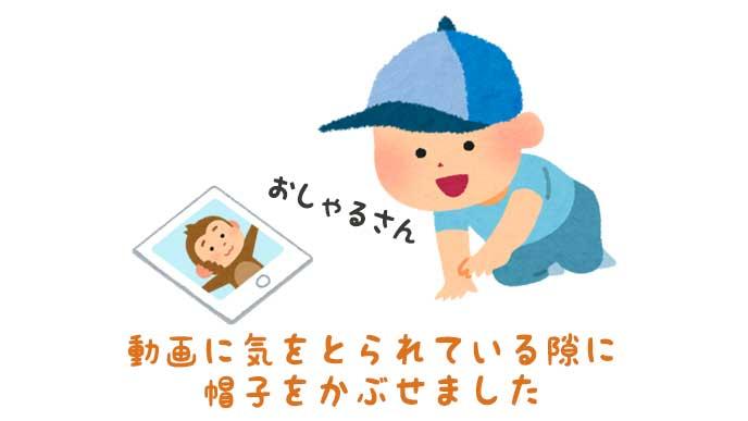 タブレットに映ったおサルさんの動画に気をとられている「帽子を被った赤ちゃん」のイラスト