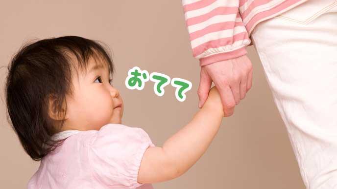 母親と手をつなぐ赤ちゃん