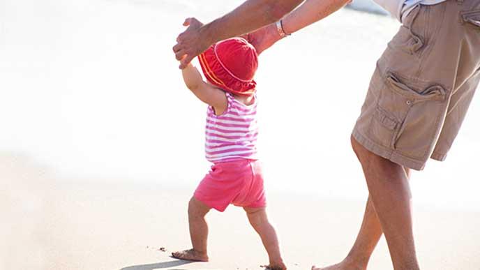 砂浜で赤ちゃんを歩かせるママ