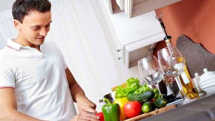 つわり中の妻の代わりにキッチンで料理を作る旦那