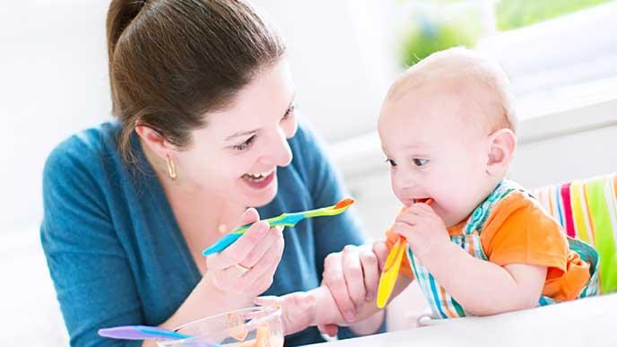 愛情を注いで子供に離乳食を食べさせる母親