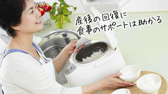 ご飯を茶碗に盛り付けるヘルパーの女性