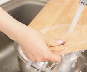 まな板を洗う女性の手