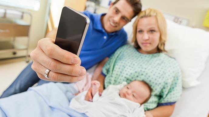 ベットの傍で夫が新生児を抱いた妻とスマホで記念撮影をする