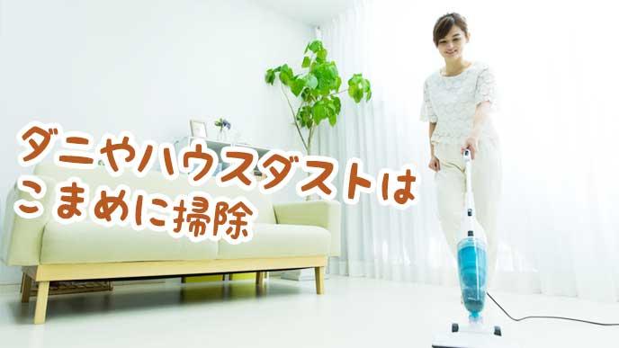 掃除機でリビングのダニやハウスダストをこまめに掃除するママ