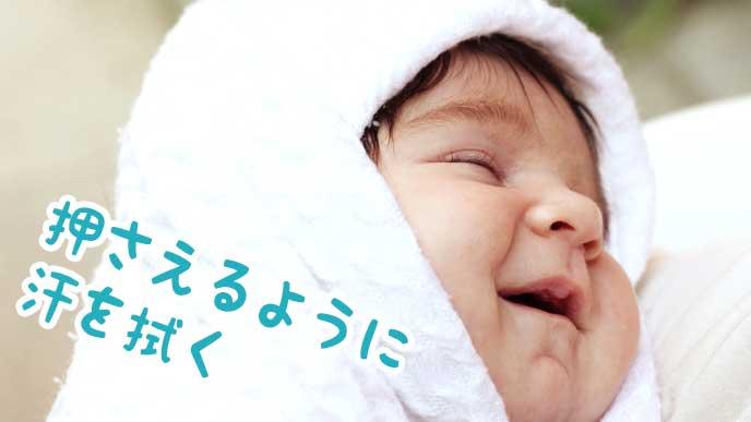 タオルを押さえて赤ちゃんの顔の汗を拭く
