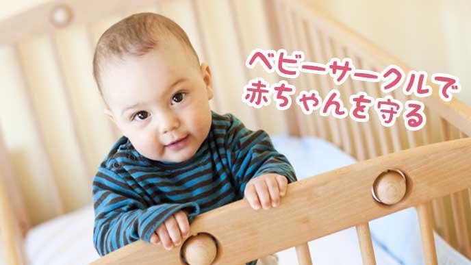 ベビーサークルの中で立っている赤ちゃん
