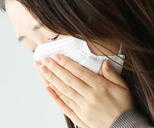マスクを押さえながら咳き込む女性