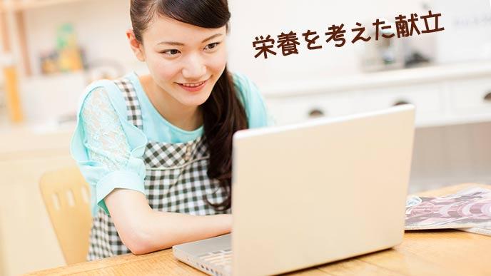 パソコンで献立を調べる女性