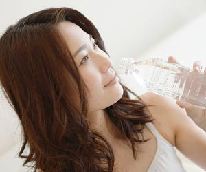 ペットボトル飲料を飲む女性