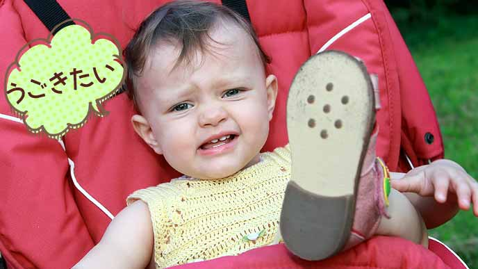 ベビーカーの上で足を上げて動きたいとぐずる赤ちゃん