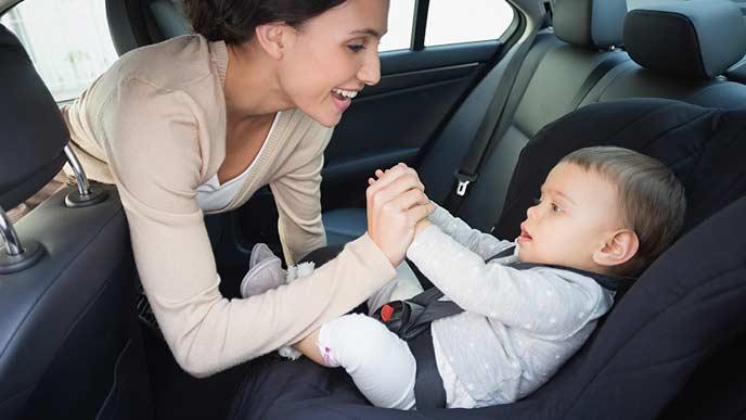 チャイルドシートに座った子供をあやす女性