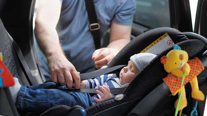 チャイルドシートに赤ちゃんを寝かせる父親