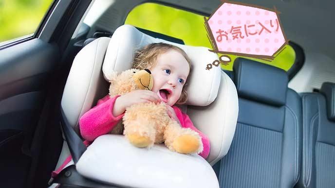 ぬいぐるみを抱いて嬉しそうチャイルドシートに座る赤ちゃん