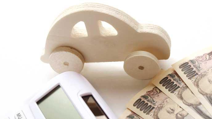 木で出来た車のオモチャとお金と電卓