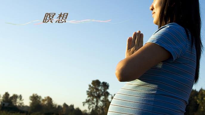 戸外で手を合わせて瞑想する妊婦