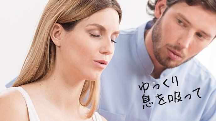 妊婦の妻の傍で一緒に呼吸法をやる夫
