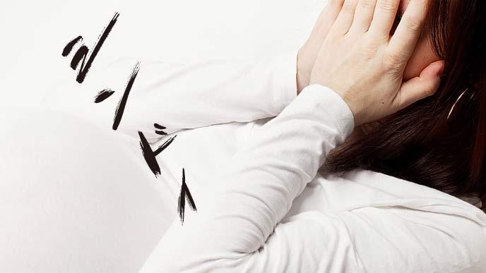 手で顔を覆い痛みに耐える妊婦