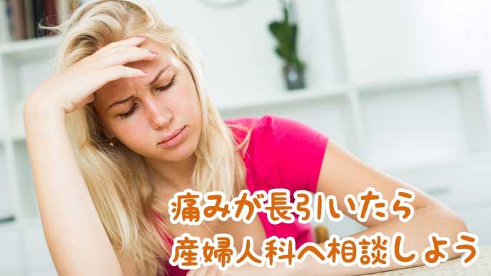 痛みに悩まされ頭を押さえている女性