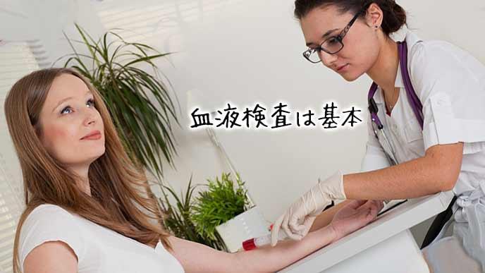 女性の腕から血液を採取する看護師
