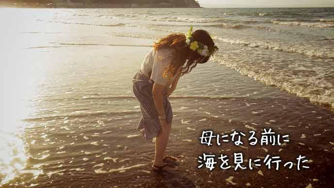 夕暮れの渚で波と戯れる女性