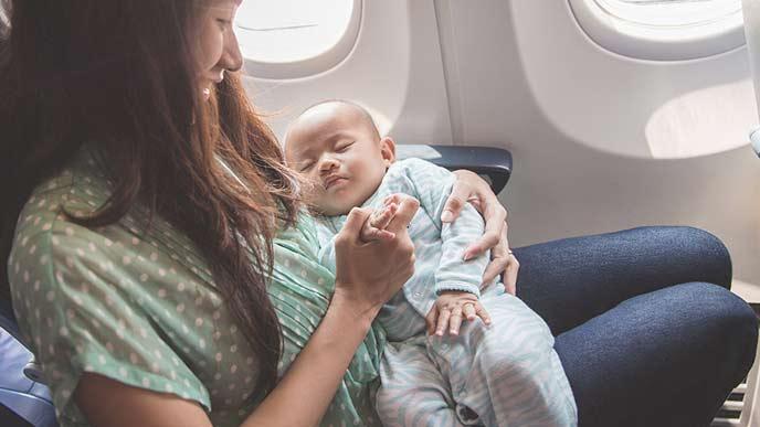 赤ちゃんと一緒に乗り物の座席に座る母親