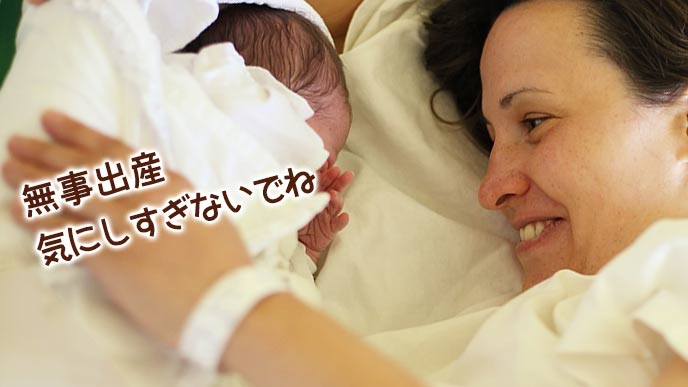 新生児を見つめる母親