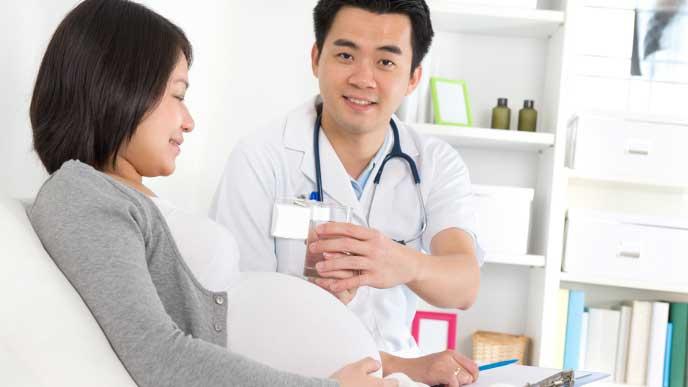 病院に入院中の妊婦と医師