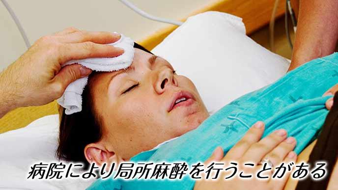 分娩台の上で目を閉じる妊婦