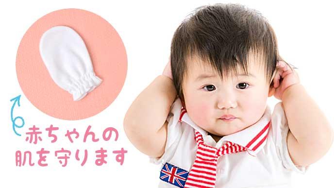 赤ちゃん用のミトンと耳を触る赤ちゃん